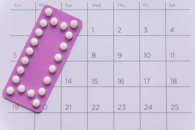 Píldora anticonceptiva con fecha de fondo del calendario, atención médica y concepto de medicina.