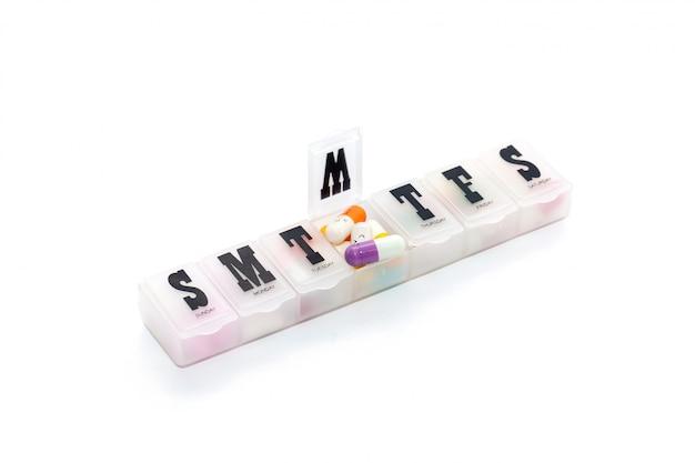 Píldora colorida en la caja en el fondo blanco