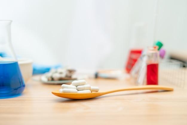 Píldora en una cuchara de madera en el laboratorio.