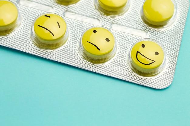 Píldoras amarillas y caras divertidas en una ampolla. el concepto de antidepresivos y curativos.