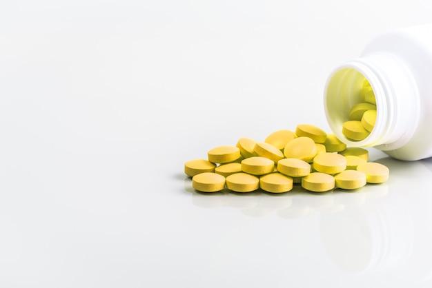 Las píldoras amarillas se dispersan de un frasco sobre un fondo blanco.