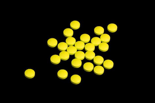Las píldoras amarillas están esparcidas sobre un fondo negro.