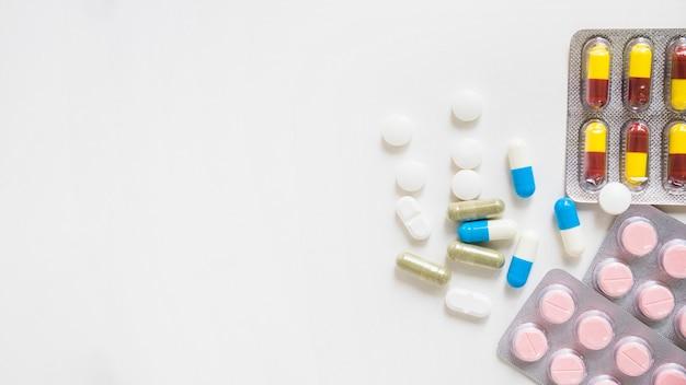 Píldoras y ampolla de la medicina en el fondo blanco