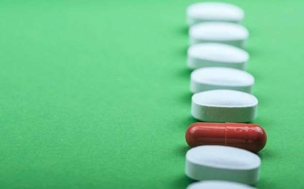 Píldoras blancas médicas y cápsulas marrones para el tratamiento y la atención de la salud sobre un fondo verde.
