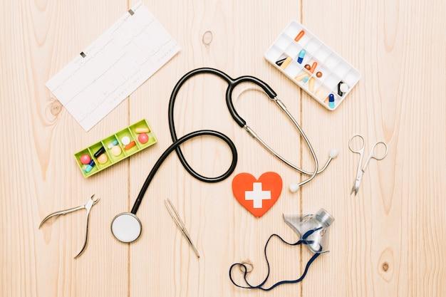 Píldoras y cardiograma cerca de suministros médicos
