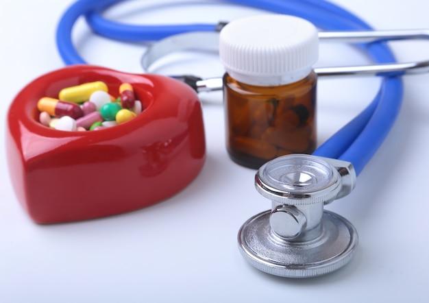 Píldoras clasificadas y un estetoscopio en el fondo blanco.