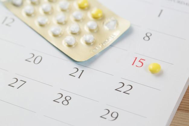 Píldoras de control anticonceptivo en la fecha del fondo del calendario. concepto de salud y medicina