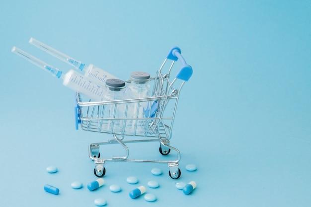 Píldoras e inyección médica en carrito de la compra sobre fondo azul. idea creativa para el concepto de negocio de costo de atención médica, farmacia, seguro de salud y compañía farmacéutica. copia espacio