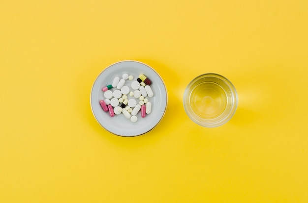 Píldoras médicas en agua del tazón y del vidrio en fondo amarillo