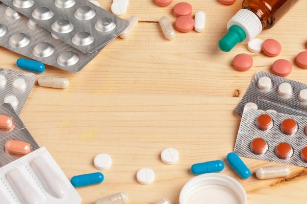 Píldoras médicas coloridas, cápsulas o suplementos para el tratamiento y cuidado de la salud sobre fondo de madera