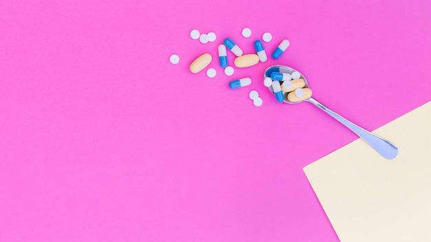 Píldoras médicas en la cuchara contra fondo rosado