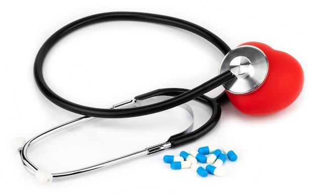 Píldoras médicas, estetoscopio y corazón en un blanco.