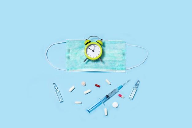 Píldoras médicas y reloj despertador, cápsulas en paquetes, una jeringa de inyector.