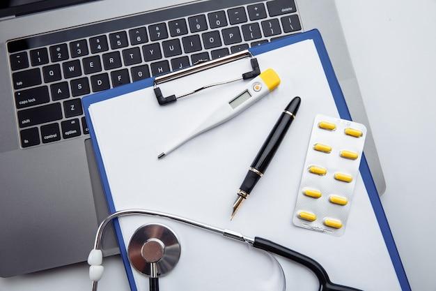 Píldoras médicas, termómetro y estetoscopio en el primer plano del formulario de reclamación médica