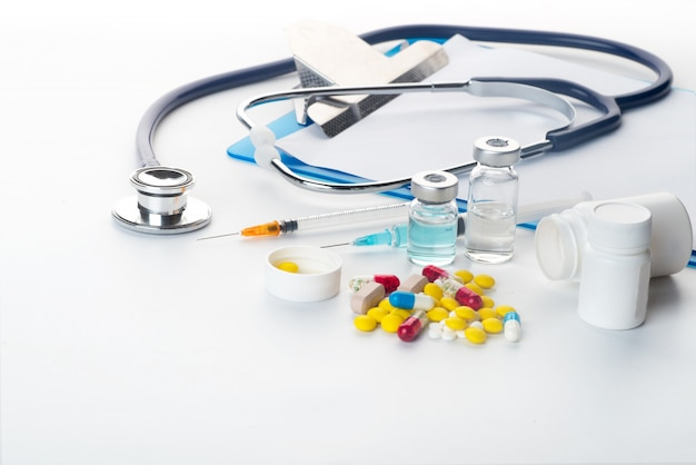 Píldoras que se derraman fuera del termómetro y del estetoscopio de la jeringuilla de la botella de píldora en el fondo blanco