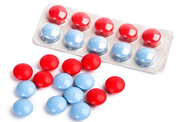 Píldoras rojas y azules en primer plano de ampolla de plástico