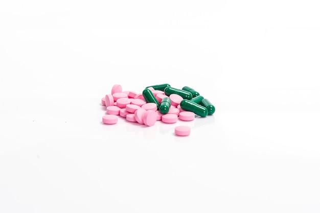 Píldoras rosadas y cápsula verde sobre fondo blanco.