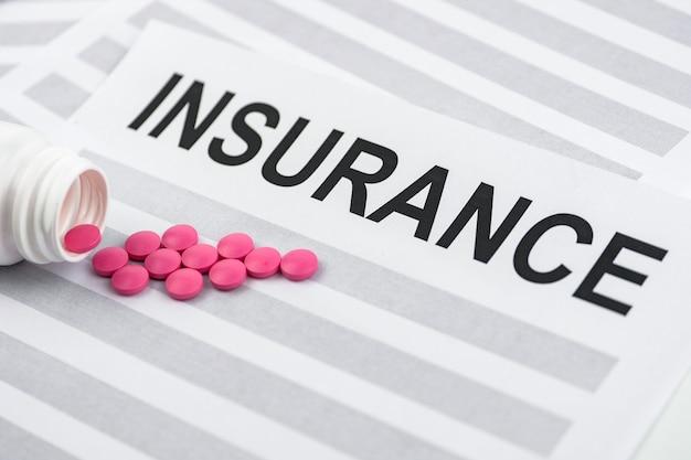 Píldoras rosadas del paquete en el contrato con el seguro.