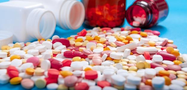 Píldoras y tabletas médicas que se derraman de una botella de droga