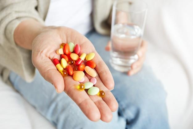 Píldoras, tabletas, vitaminas y medicamentos se amontonan en manos maduras