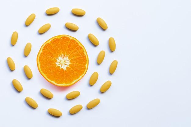 Píldoras de vitamina c con fruta naranja sobre fondo blanco con copyspace