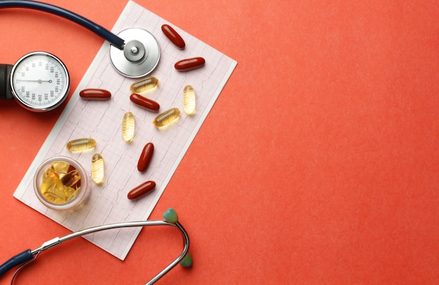 Píldoras, vitaminas, estetoscopio, cardiograma, sobre la mesa. copie el espacio.