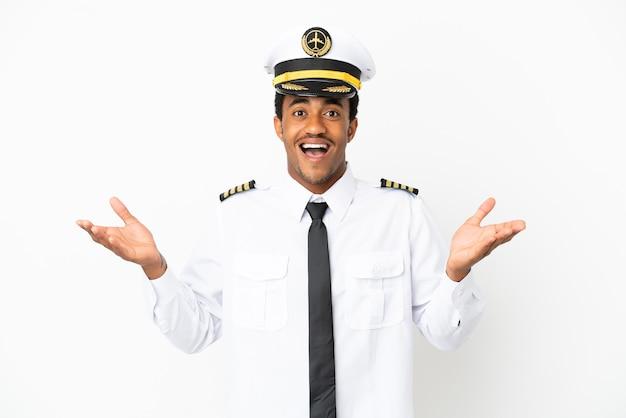 Piloto de avión afroamericano sobre fondo blanco aislado con expresión facial conmocionada