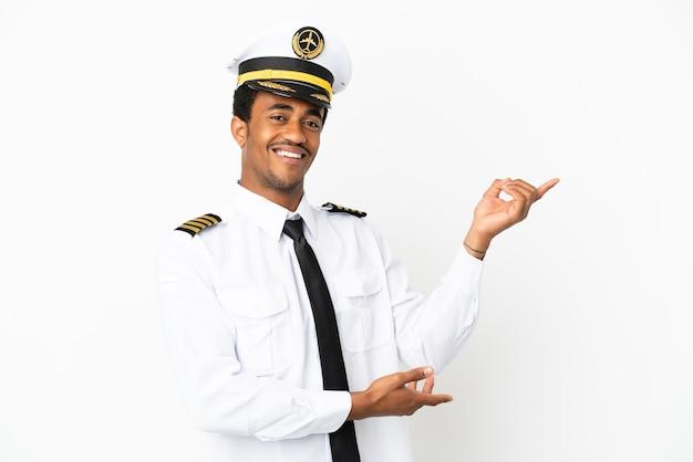 Piloto de avión afroamericano sobre fondo blanco aislado extendiendo las manos hacia el lado para invitar a venir