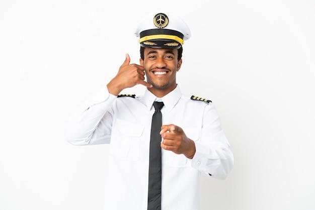Piloto de avión afroamericano sobre fondo blanco aislado haciendo gesto de teléfono y apuntando hacia el frente