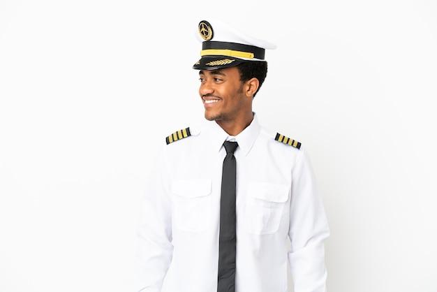 Piloto de avión afroamericano sobre fondo blanco aislado mirando de lado