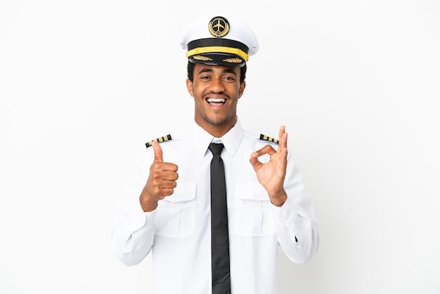 Piloto de avión afroamericano sobre fondo blanco aislado que muestra el signo de ok y el pulgar hacia arriba gesto