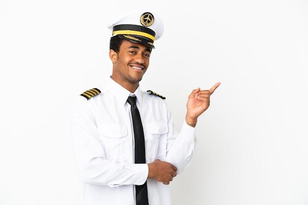Piloto de avión afroamericano sobre fondo blanco aislado que señala el dedo hacia el lado