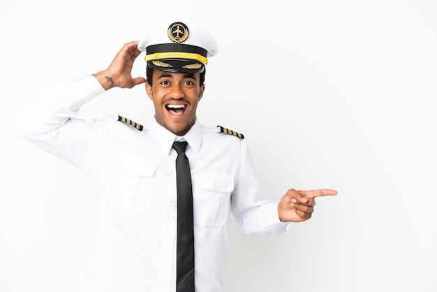 Piloto de avión afroamericano sobre fondo blanco aislado sorprendido y apuntando con el dedo hacia el lado