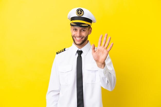 Piloto de avión caucásico aislado sobre fondo amarillo saludando con la mano con expresión feliz