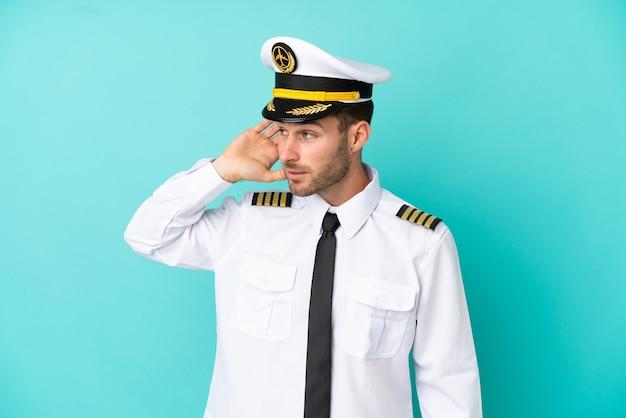 Piloto de avión caucásico aislado sobre fondo azul escuchando algo poniendo la mano en la oreja