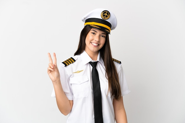Piloto de avión chica brasileña sobre fondo blanco aislado sonriendo y mostrando el signo de la victoria