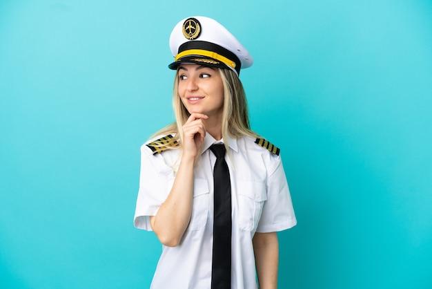 Piloto de avión sobre fondo azul aislado mirando hacia el lado y sonriendo