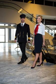 Piloto y azafata caminando con sus maletas trolley