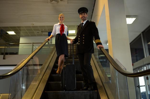 Piloto y azafata con sus maletas con ruedas de pie en la escalera mecánica