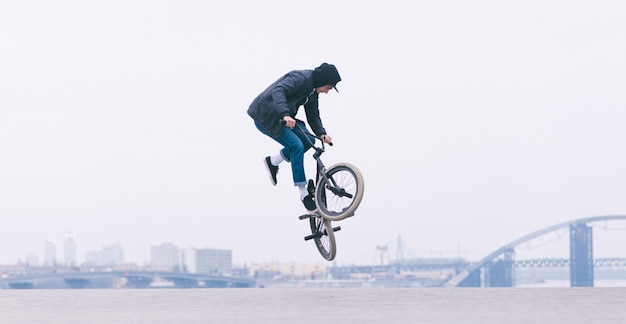 El piloto de bmx hace un truco tailwhip. joven haciendo trucos en el aire en una bicicleta bmx. bmx estilo libre