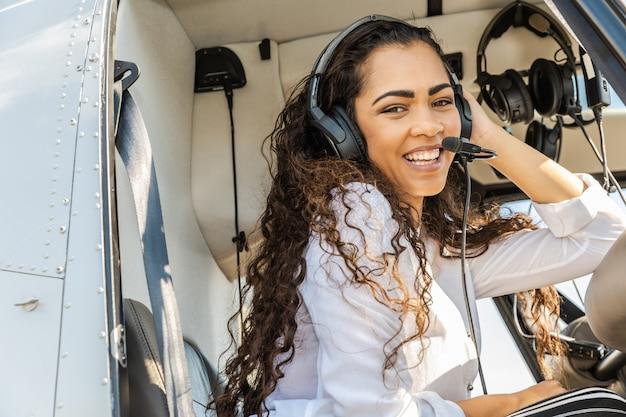 Piloto de helicóptero de mujer sonriente joven