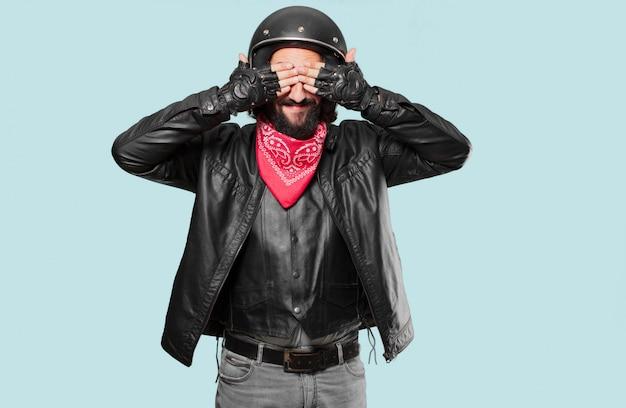 Piloto de moto cubriendo sus ojos.