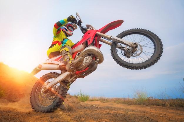 Piloto de motocross haciendo un wheelie.