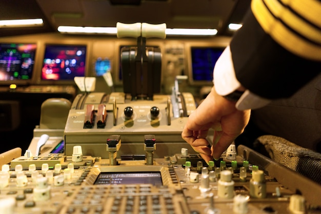 Piloto en uniforme en cabina de avión está sintonizando el panel de radio.