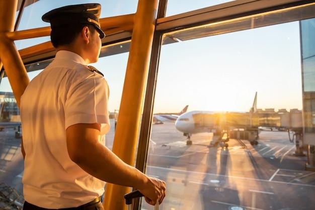 Piloto en uniforme de pie en el área de la puerta de embarque en la terminal del aeropuerto mirando por la ventana para ver al personal de tierra preparando un avión.