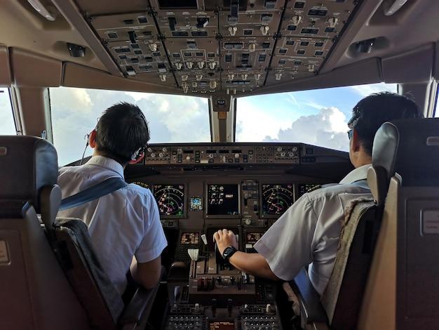 Pilotos comerciales asiáticos en carlinga operando el avión para evitar el clima nublado