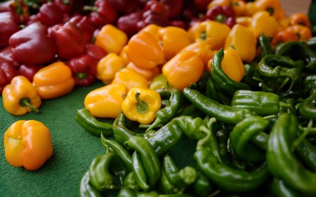 Pimentón rojo, amarillo, pimentón y pimiento verde saludable en el mercado agrícola de agricultores