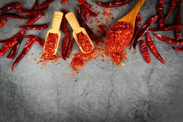 Pimienta de cayena en especias de cuchara de madera y chiles secos, grupo de chile rojo en polvo en placa negra vista superior ingredientes mesa comida asiática picante en tailandia