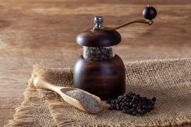 Pimienta negra y molinillo de pimienta en el piso de madera