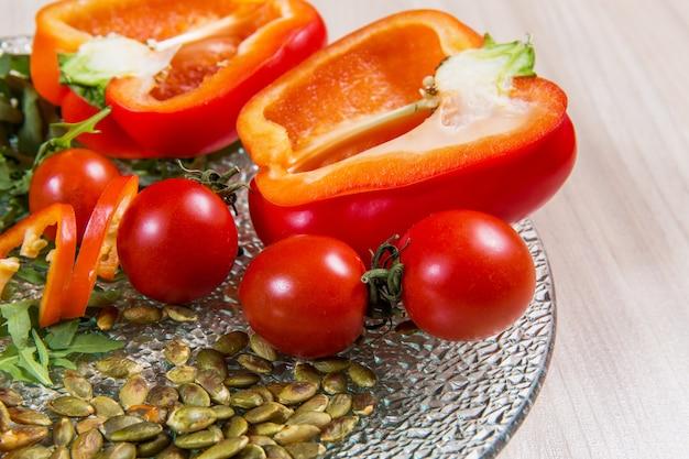 Pimienta roja con los tomates cereza y semillas en la placa de cristal n mesa de madera ligera. ingredientes en placa